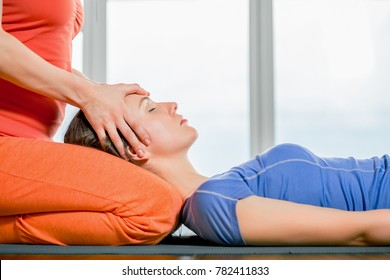 Close up portrait young beautiful girl making face head massage. Model lying on the knees of a masseuse in a yoga studio