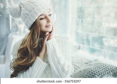 Close up portrait of young beautiful happy smiling girl touching her face, closed eyes. Model wearing stylish clothes. Day light from window, white room as background. Copy space for text. Toned