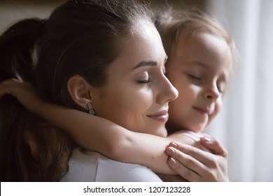 Close up portrait young beautiful sincere woman mother embrace hug little preschool girl daughter make peace after quarrel. Happy motherhood, custody guardianship new mother for adopted child concept