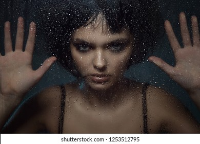 Close up portrait of young beautiful woman with provocative make up and stylish bob haircut standing behind the window with rain drops on it and touching the glass with her palms