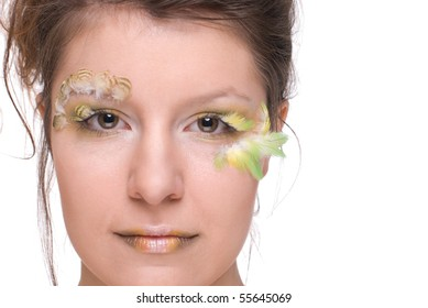 Close up portrait of young and beautiful woman with  feather make up and art
