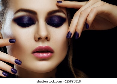 Close up portrait of young beautiful woman with healthy flawless skin, big pink lips, smokey eye make up, dark purple nails posing on black background. Model touching her face. Female beauty concept