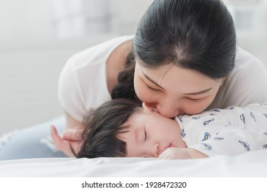Close up portrait of young beauty Asian mother kissing her newborn baby boy while he sleep. Healthcare and medical insurance. Asia mother's day concept banner.