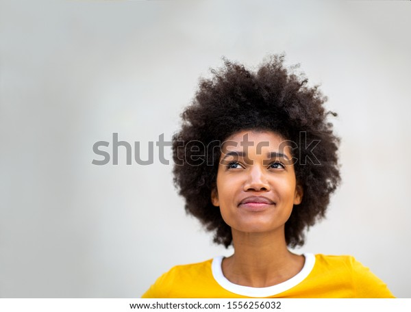 Close up portrait of young black woman thinking and looking up