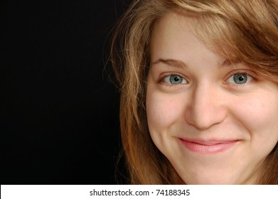 A Close Up Portrait of a Young Blond Girl Smiling with a Black Background and Room for Text