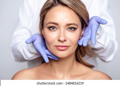 Nahaufnahme eines Porträts junger blonder Frauen mit Kosmetologen in Handschuhen. Vorbereitung auf den Betrieb oder das Verfahren. Perfekte Haut, Spa und Pflege