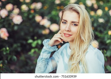 Close up portrait of a young blondie stylish beautiful girl sitting in a park and have a good time outdoors in summer