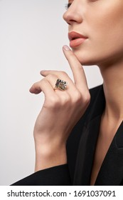 Close up portrait of young brunette female model in formal black suit presenting golden and silver earrings and ring. Crop of woman posing in studio, isolated on white background. Concept of jewelry.