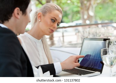 Close up portrait of young business couple reviewing work on laptop at lunch.