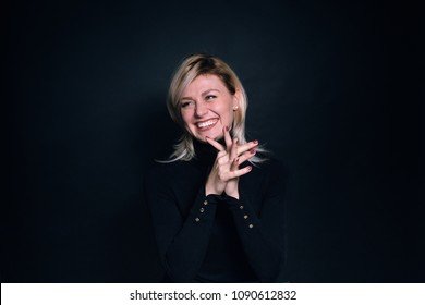 Close up portrait of a young business woman, laughing and looking to the side, against a plain studio background
