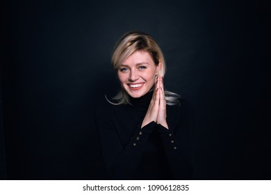Close up portrait of a young business woman, smiling and looking at the camera, against a plain studio background