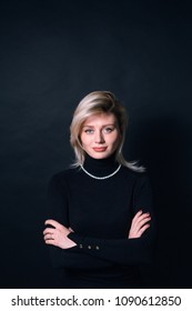 Close up portrait of a young business woman, looking at the camera, against a plain studio background