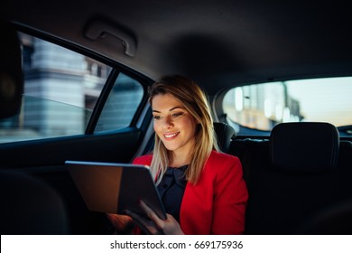 Close up portrait of a young business woman using digital tablet in the back seat of the car.