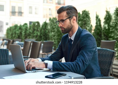 Close up portrait of a young businessman with a beard and wearing glasses who is sitting and looking at the laptop