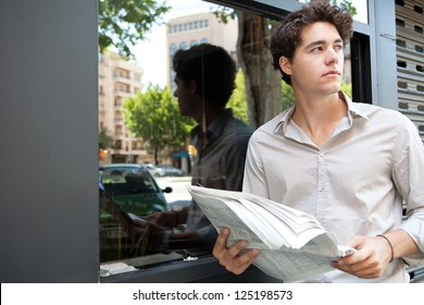 Close up portrait of a young businessman holding a newspaper and standing in the city by a glass window with reflections of office buildings.