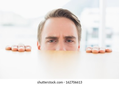 Close up portrait of a young businessman looking over blurred wall at bright office