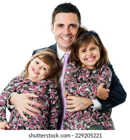 Close up portrait of young businessman in suit holding his two little daughters.Isolated on white background.