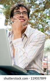Close up portrait of a young businessman using a laptop computer while sitting on a bench in a city park, outdoors.