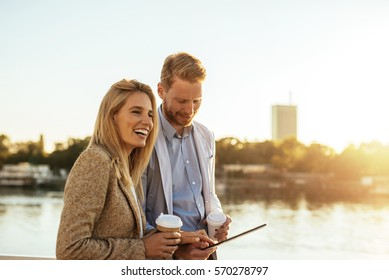 Close up portrait of young businesspeople discussing about a project by the river. They are both happy. A man is holding a digital tablet while she is holding a coffee.