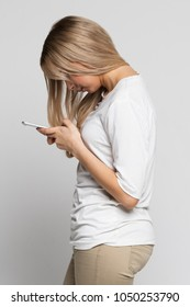 Close up portrait of young Caucasian female looking and using smart phone with scoliosis, side view/Rachiocampsis/Kyphosis curvature of the spine/Incorrect posture, scoliosis,  orthopedics concept