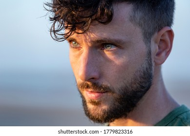 Close up portrait of a young caucasian handsome man opening his blue eyes during the sunset