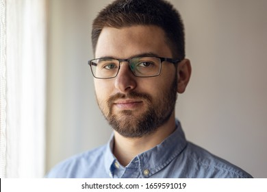 Close up portrait of young caucasian man adult wearing shirt and eyeglasses standing by the window front view short hair and beard