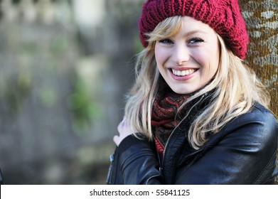 Close up portrait of young caucasian woman outdoors, leaning against a tree
