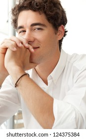 Close up portrait of a young confident businessman wearing a white shirt and smiling at the camera while leaning on his hands with interlinked fingers.
