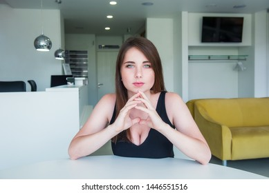 Close up portrait of a young confident serious woman with deep decollete, looking at the camera, holding hand near the face, looking seriously up against a office hall background. Copy space