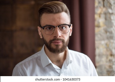 Close up Portrait of young confident smiling businessman in smart casual wear in office.