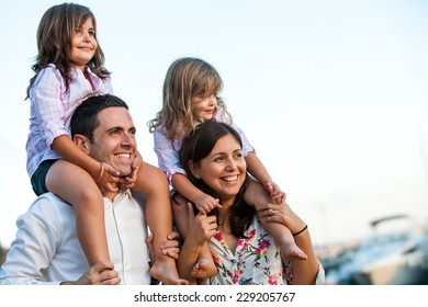 Close up portrait of young couple with kids on shoulders at sunset.