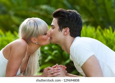 Close up portrait of young couple kissing in park.