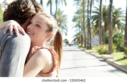 Close up portrait of a young couple on vacation hugging while visiting a destination city during a sunny day.