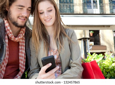 Close up portrait of a young couple on vacation in a destination city, sitting down with shopping bags and using a smartphone device during a sunny day.