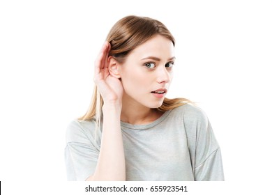 Close up portrait of a young curious girl trying to hear rumors isolated over white background