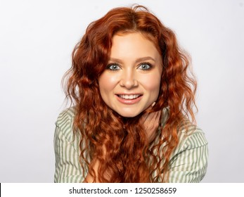 Close up portrait of young curly redhead girl on white background.