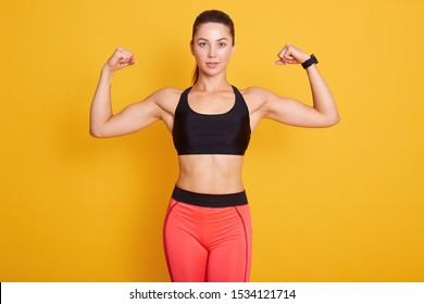Close up portrait of young cute sporty brunette woman with ponitail, showing her arms and biceps to camera, female wears black bra and leggins. Sport, healthy lifestyle, women health, fitness concepts