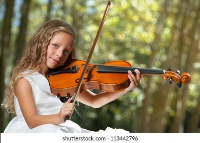 Close up portrait of young cute violinist playing in the woods.