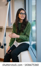 Close up portrait of a young, educated, confident and intelligent-looking Indian Asian student girl smiling as she sits in a seminar room by the window during the day in a preppy outfit.
