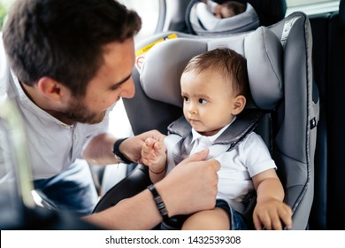 close up portrait of young father securing baby in child seat of car