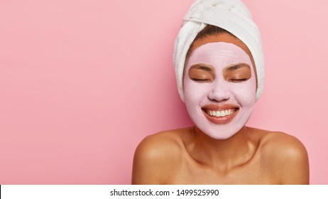 Close up portrait of young female model applies homemade facial clay mask, has white towel wrapped around head, keeps eyes shut, smiles happily, models against pink background. Beauty treatment