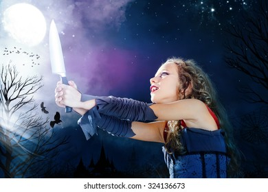 Close up portrait of young female vampire holding big knife. Castle towers and crows flaying in full moon background.