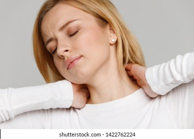 Close up portrait of young female in white top touching her pain in her neck and back, feels pain, massages the painful area. Cervical arthritis, osteochondrosis, diseases of musculoskeletal system