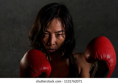 close up portrait of young fit and healthy Asian Chinese woman in fitness top and boxing gloves posing cool in bad ass attitude angry and defiant in combat and fight training isolated on dark grunge