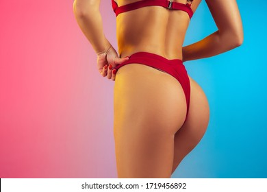 Close up portrait of young fit and sportive caucasian woman in stylish red swimwear on gradient background. Brunette longhair model. Perfect body ready for summertime. Beauty, resort, sport concept.