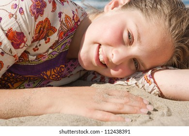 Close up portrait of a young girl laying down on a golden sand beach, smiling.