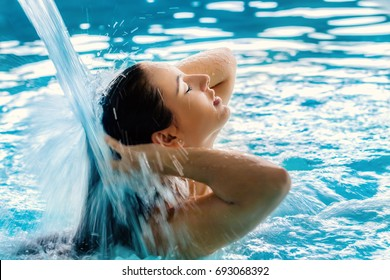 Close up portrait of young girl with relaxed facial expression under high pressure shower in spa.Woman touching hair with eyes closed.