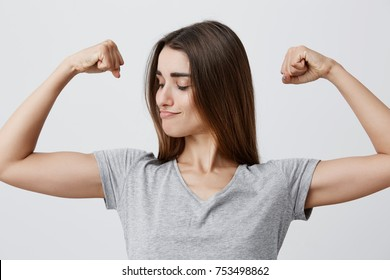 Close up portrait of young good-looking funny caucasian brunette girl with long hair in t-shirt playing with muscles, looking at them with confident and powerful face expression. Health and beauty