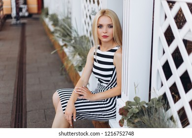 Close up portrait of young gorgeous blondie caucasian sexy girl outdoors in summer in the european streets walking in fashionable stylish dress