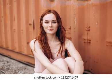 Close up portrait of young gorgeous cute natural girl with long red hair and freckles posing and have fun outdoors on cooper background. Happiness, beauty, freedom concept
